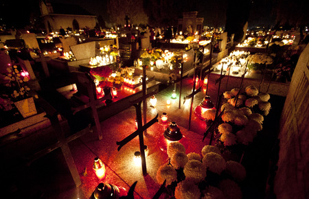 Candle flames illuminating  cemetery during All Saints Day photo
