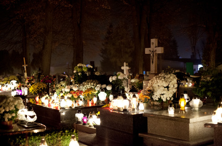 hallowmas: Candle flames illuminating  cemetery during All Saints Day Editorial