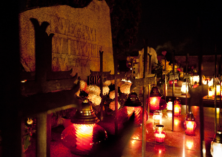 Candle flames illuminating  cemetery during All Saints Day Editorial