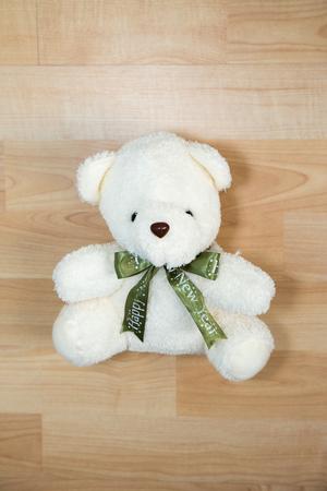 white wood floor: white bear doll on wood floor