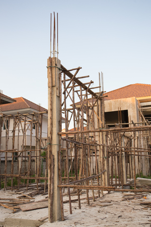 staging: wood staging and concrete pole of house at construction site