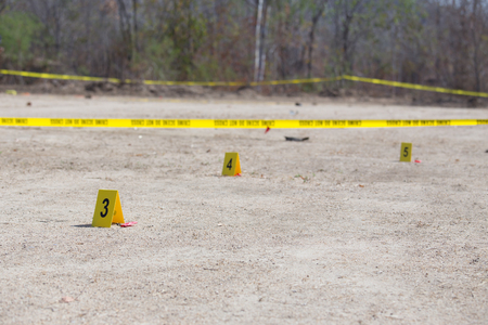 crime: evidence number tag and crime scene tape in crime scene