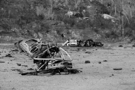 blown away: wrecked car from car bomb in black and white color