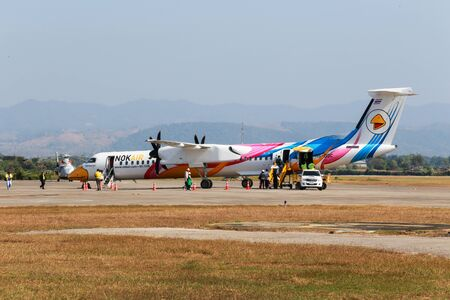 bombardier: Mae Sot, Thailand DEC 20, 2014: Unidentified group of people walked to BOMBARDIER Q400 NextGen Nok Kao Poon of Nok Air at Mae Sot Airport. The Airport located at western end of Thailand near Thailand - Myanmar border