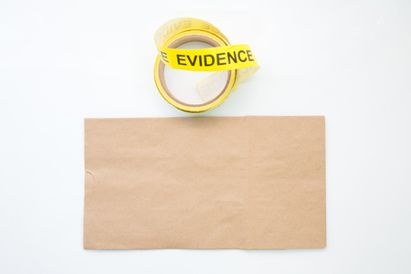 background csi: blank paper evidence bag with yellow protection tape on white background Stock Photo
