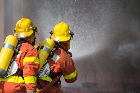 pyromania: 2 firefighters in protection suit spraying water in fire fighting operation