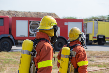 pyromania: 2 firefighters in fire protection equipment and fire truck background