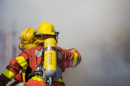 fire surround: firefighter and rescue team in fire protecction suit and equipment  work surround with smoke and dust