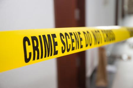 investigación: cinta de la escena del crimen delante de puerta de la habitación con el fondo borroso Foto de archivo