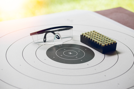 shooting target: vintage paper shooting target with box of 9 mm bullet and protection glassess at shooting range with flare