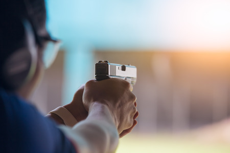 law enforcement aim pistol by two hand in academy shooting range in flare and vintage color