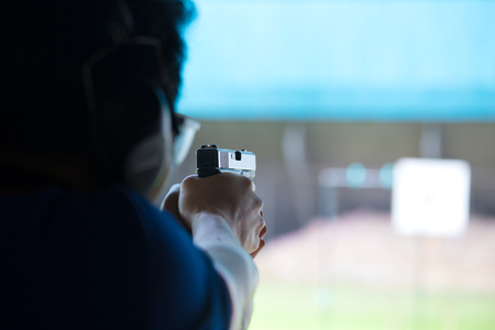 taget: a man aim and shoot pistol to white paper target by two hand in academy shooting range focus on gun Stock Photo