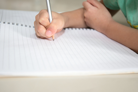 pratice: child hand writing on blank notebook pencil  and copy space in vintage tone