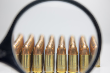 crime scene investigation: row of 9 mm bullet zoom by detectives  magnifying glass in crime scene investigation