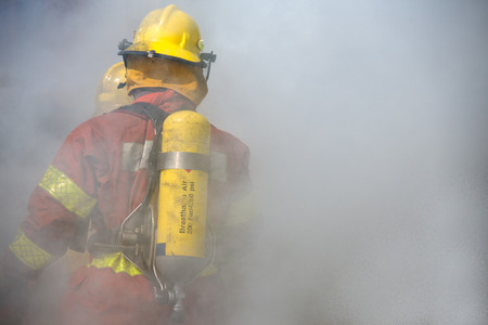 fire surround: fireman in fire fighting suit working surround with smoke