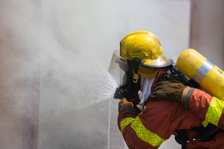 fire surround: firefighter in fire protection suit spraying water to fire surround with smoke and drizzle in training Stock Photo