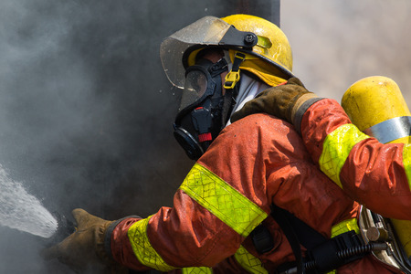 fire surround: fireman in fire fighting suit spraying water to fire surround with smoke and drizzle close up