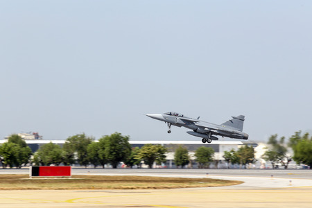 max: jet fighter aircraft with landing gear take off from runway with max power