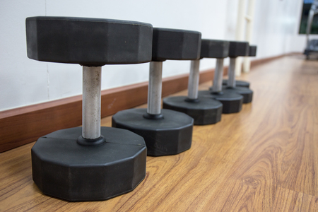 muscle building: group of dumbbells for muscle building on on wood floor  in workout room Stock Photo