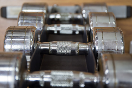 weight room: close up group of dumbbells for weight training on rack in workout room