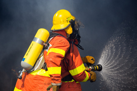 2 firemen use hydrant nozzle fighting with fire surround with dark smoke
