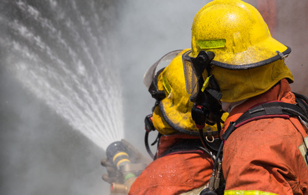 two firemen in helmet and oxygen mask spraying water to fire surround with smoke and dust Stock Photo