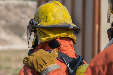 law suit: firefighter hand put on shoulder of first man for signal in fire fighting teamwork