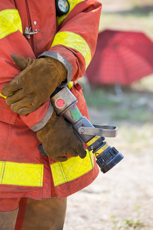 standby: fireman hand in work suit and glove hold fire branch in standby position