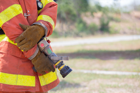 pyromania: fireman hand in work suit and glove hold fire branch in standby position