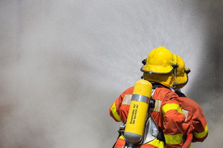 pyromania: two firefighter in fire fighting suit spraying high pressure water to fire and smoke Stock Photo