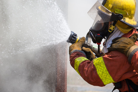 fire surround: fireman in fire fighting suit spraying water to fire surround with smoke and drizzle Stock Photo