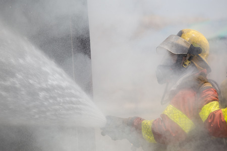 oxygen mask: fireman in helmet and oxygen mask  spraying water to fire surround with smoke and drizzle Stock Photo