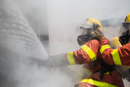 fire surround: two firemen in oxygen mask helmet and fire fighting suit spraying water to fire surround with smoke and drizzle