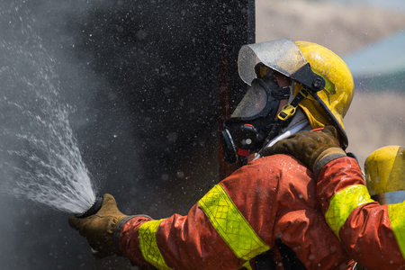fire surround: fireman in helmet and oxygen mask  spraying water to fire surround with smoke and drizzle Stock Photo
