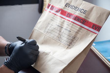 de hand forensische 's in zwarte handschoen schrijven op bewijs zak en afdichting door de bureaucratie in crime scene investigation