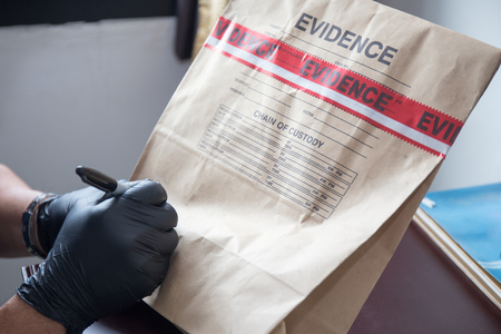 mano s 'forense per iscritto guanto nero sul sacchetto di prove e sigillare con nastro rosso in indagini della scena del crimine