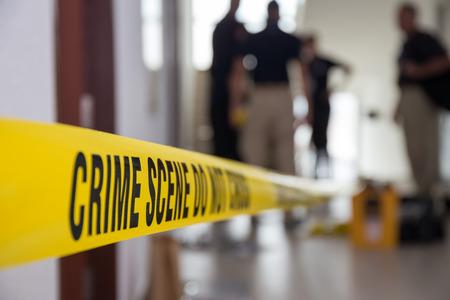 band van de misdaadscène in gebouw met onscherpe forensisch team achtergrond