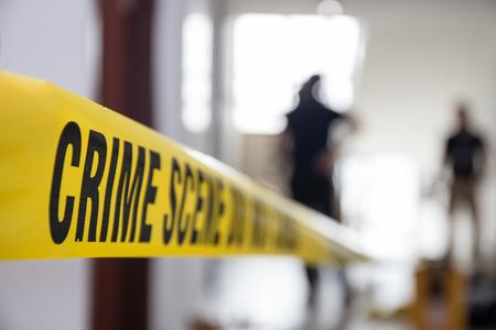 cinta de la escena del crimen en la construcción con el fondo borroso equipo forense