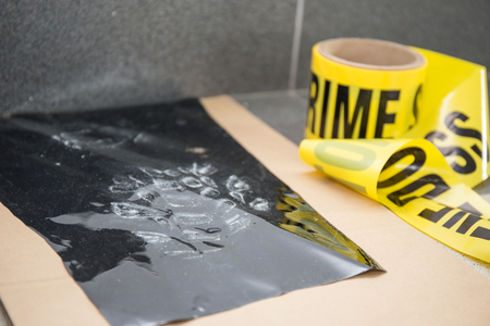 evidence bag: latent footprint evidence with crime scene tape in crime scene investigation Stock Photo