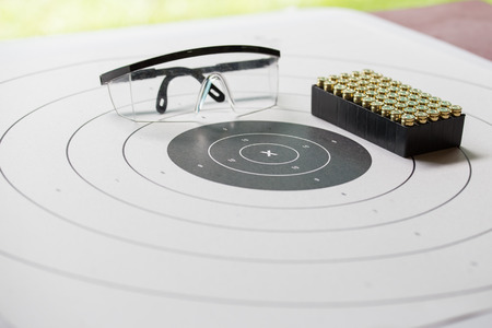 shooting target: paper shooting target with safety glasses and 9 mm bullet for shooting practice in law enforcement academy shooting range focus on X Stock Photo