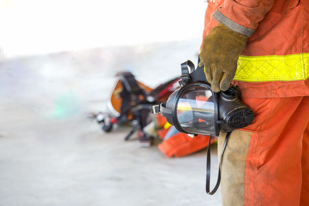 fireman hand in glove hold oxygen mask Stock Photo
