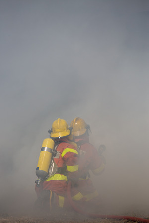 fire surround: two firefighters is working surround with smoke Stock Photo