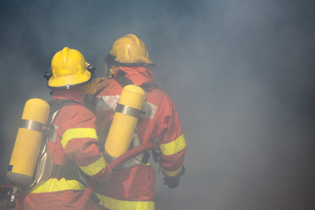 fire surround: two firefighters is working surround with smoke and dust
