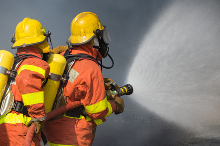 2 firefighters spraying water in fire fighting with dark smoke background Imagens - 65315640