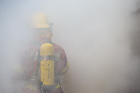 fire surround: single fireman in operation surround with smoke