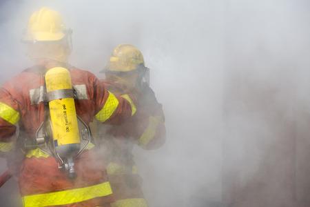 fire surround: 2 firemen in operation surround with smoke Stock Photo