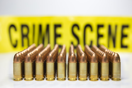 full jacket bullet: row of bullet with crime scene tape background Stock Photo