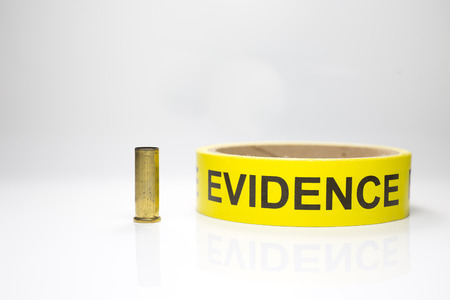 csi: evidence tape with brass bullet case on white background