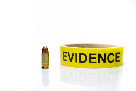 background csi: evidence tape with 9 mm bullet  on white background
