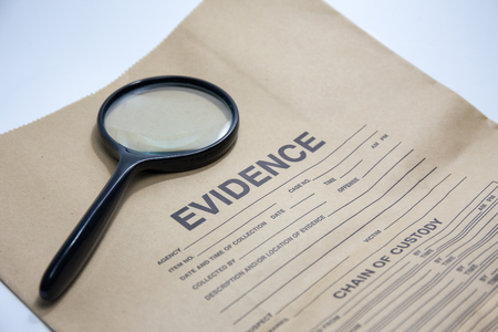 evidence bag: magnifying glass with evidence brown paper bag